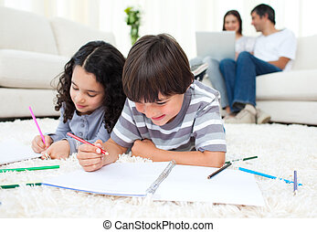 Beautiful siblings drawing lying on the floor at home