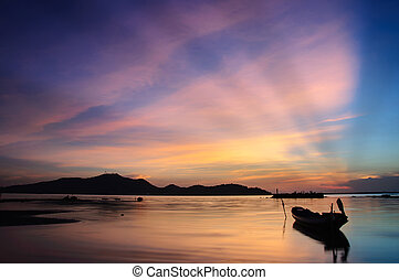 Beautiful silhouette fishing boat in lake at Twilight sky.