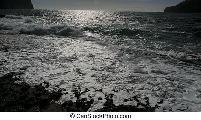 Beautiful silky smooth water waves and rocks on the sea shore during the sunny day.