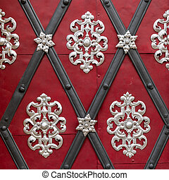 Beautiful silver decoration on a red door