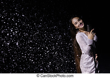 Beautiful singer posing with a vintage microphone against the background of falling snow. Snowflakes glisten in studio light. Close up.