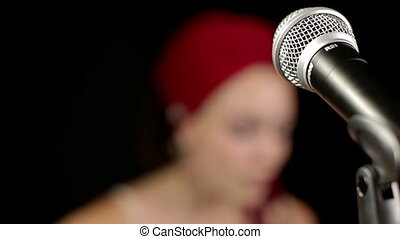beautiful singer with a red wrap around her head, focus changes from microphone to her