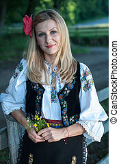 beautiful singer with flowers posing in traditional costume,...