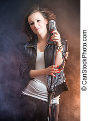 Beautiful singer with microphone on stage