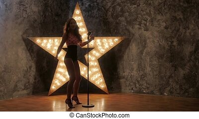 Beautiful Singing Girl. Beauty Woman with Microphone, shining star in the background