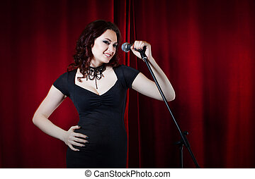 Beautiful Singing Girl on stage. Beauty Woman with Microphone. Red curtain  background