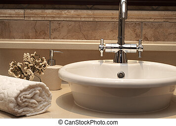 Beautiful sink in a bathroom with rolled up towel next to it...