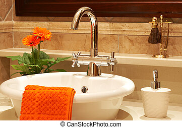 Beautiful sink in a bathroom with towel on it and a flower....