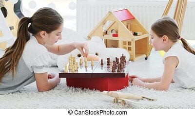 Beautiful sisters playing chess lying on floor in kids room