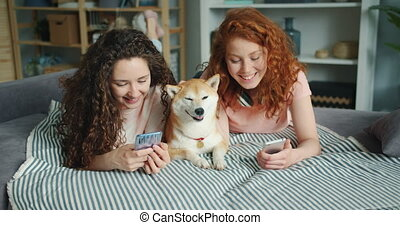 Beautiful sisters using smartphone and petting cute doggy ...