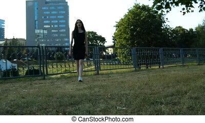 beautiful skinny brunette slowly walks on green grass in the...