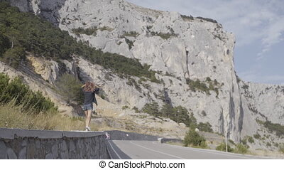 Beautiful skinny girl running along the parapet on the background of rocks