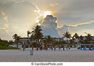 beautiful sky and people playing volleyball at the beach - ...