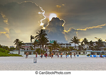 beautiful sky with clouds and people playing volleyball at ...