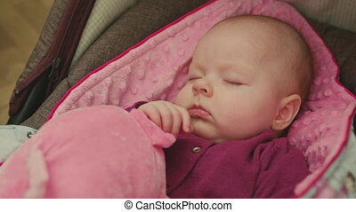 Peaceful Baby Sleeping in a Car Seat on pink blanket holding hand on a pink toy
