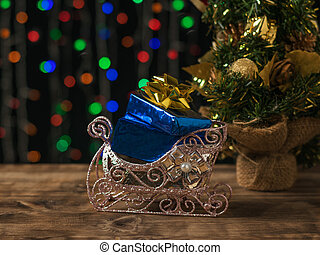 Beautiful sleigh with gifts near the Christmas tree on the background of colorful bokeh.