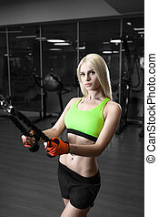 Beautiful slender girl doing exercises in the gym