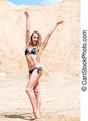 beautiful slender girl in a black bikini on the sand posing