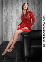 beautiful slender girl in red dress sits regional having...