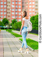 beautiful slender girl walking around the city with a backpack, rear view