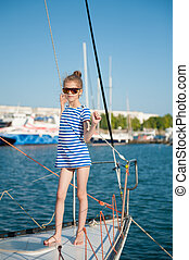 beautiful slender little girl in a striped t-shirt and sunglasses aboard luxury boat
