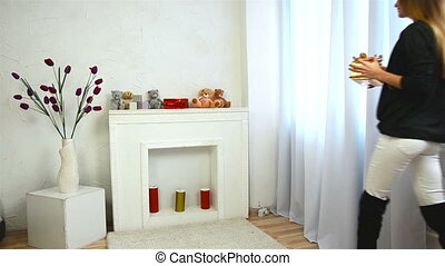 beautiful slender women coming to the fireplace puts the Golden gift box