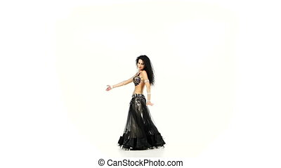 Beautiful slim belly dancer with dark hair dancing and shaking her hips, on white, slow motion