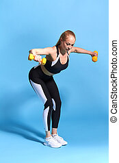 Beautiful slim blonde fitness sexy girl doing exercise with yellow dumbbells
