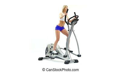 Beautiful slim blonde on exerciser