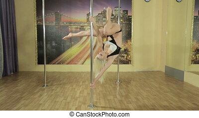 Beautiful slim girl doing amazing tricks on the pole