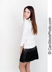 Beautiful slim girl in a short black skirt and white blouse, posing