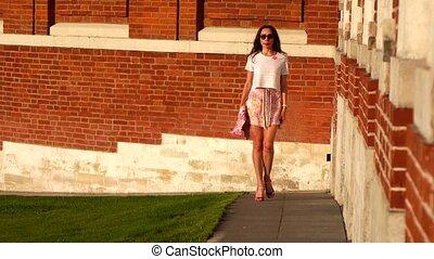 Beautiful slim girl in high heels walking near red brick wall, 4K zoom our shot