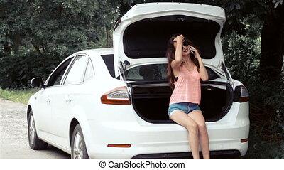 beautiful slim girl sitting in a white chic car