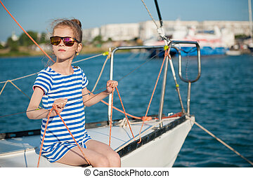beautiful slim little girl in a striped t-shirt and sunglasses sitting on board of luxury white yacht in summer cruise