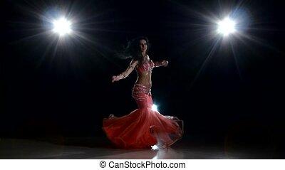 Beautiful slim woman belly dancer dancing, on black, back light