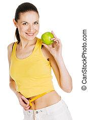Beautiful slim woman holding a green apple