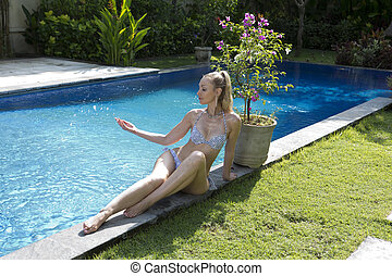beautiful slim woman in an open bathing suit sits on the edge of the pool and looks at the spray of water