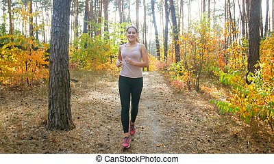 Beautiful slim woman jogging in park at bright sunny morning