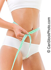 Beautiful slim woman measuring her waist. Isolated over...