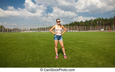 slim woman standing on soccer field at sunny day