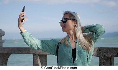 Beautiful slim woman with long blonde hair in sunglasses and green shirt standing near palm tree and making selfie on mobile phone on a blue sky and sea background. Girl using smartphone