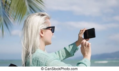 Beautiful slim woman with long blonde hair in sunglasses and green shirt standing near palm tree and take a pictures by smartphone on a blue sky background.