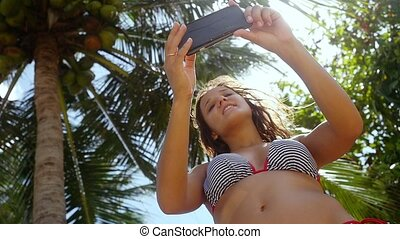 Beautiful slim woman with long brunette hair standing near palm tree and making selfie on mobile phone on a blue sky and sea background. Girl using smartphone. slow motion. 1920x1080