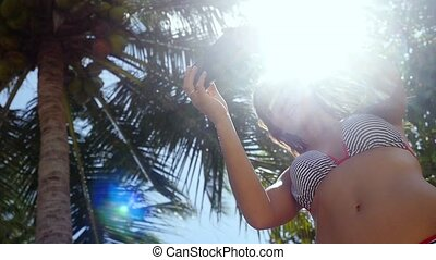 Beautiful slim woman with long brunette hair standing near palm tree and making selfie on mobile phone on a blue sky and the sun with lens flare effects background. Girl using smartphone. slow motion.