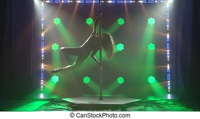 Beautiful slim woman with pylon. Female pole dancer woman dancing on a pole . Strong and graceful woman dancing on pylon. Sexy Girl Strip plastic. Silhouette sexy pole dancer. Slow motion.
