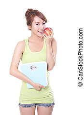 Beautiful slim woman with scales and apple