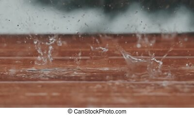 Beautiful slow motion b-roll footage of heay rain falling on...