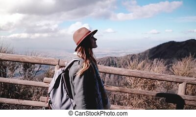 Beautiful slow motion shot of young European female travel blogger walking along Vesuvius volcano pathway slow motion. Happy female fashion blogger enjoying the landscapes from a mountain road.