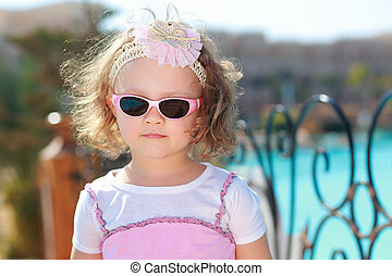 Beautiful small girl in sunglasses on blue sea background