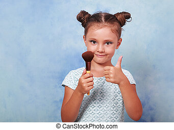 Beautiful small kid girl applying tonal cosmetic brush and...